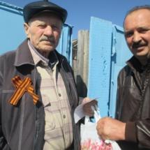 Член ТОС Кулахметов И.Р. вручает продуктовые наборы труженникам тыла 9 мая 2015 года